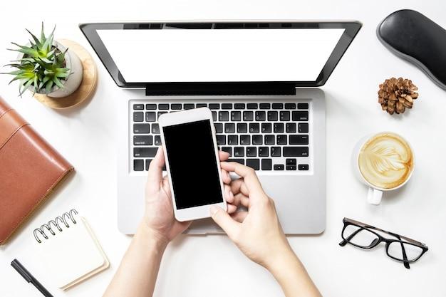 Homme utilisant un smartphone sur un ordinateur portable