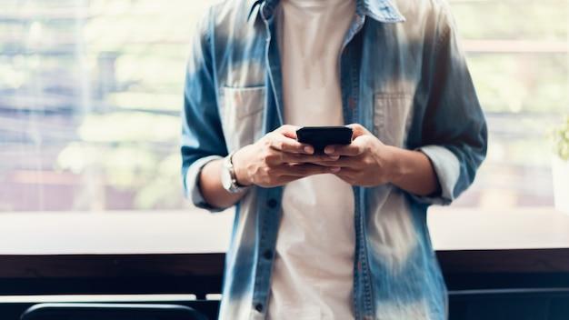 Homme utilisant un smartphone, pendant les loisirs