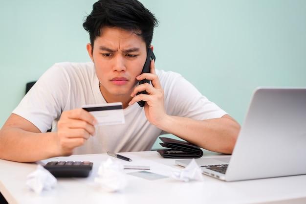 Homme utilisant un smartphone pour appeler pour parler à un opérateur bancaire qui lui pose des questions sur le paiement