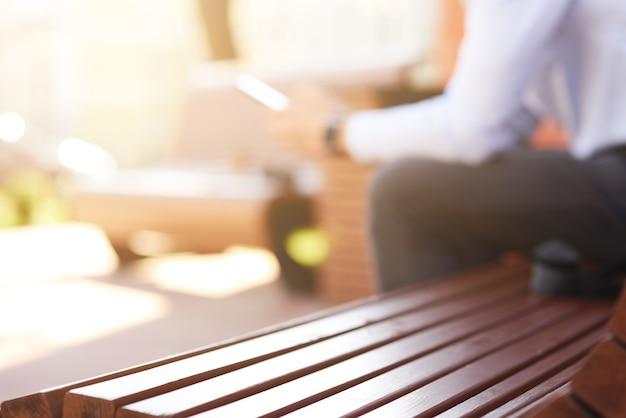 Homme utilisant un smartphone et souriant assis à l'extérieur se concentrer sur un banc en bois