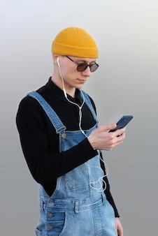 Homme utilisant un smartphone tout en écoutant de la musique avec des écouteurs. l'homme porte un chapeau jaune et des lunettes de soleil