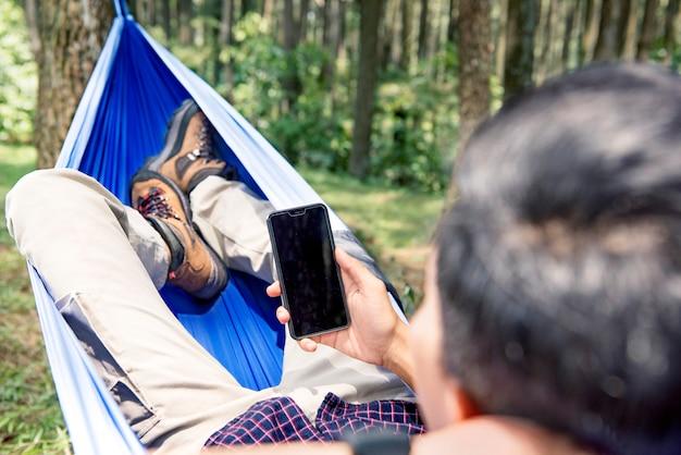 Homme utilisant son téléphone portable tout en se relaxant dans un hamac