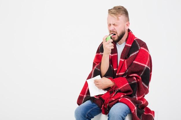Homme utilisant un spray pour le mal de gorge