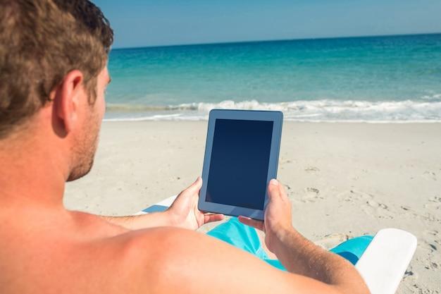 Homme utilisant une tablette numérique sur une chaise longue à la plage par une journée ensoleillée