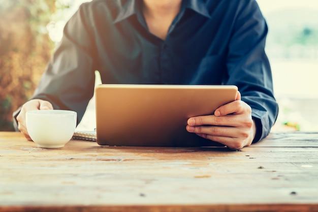 Homme utilisant une tablette sur table dans un café avec un filtre tonique vintage.