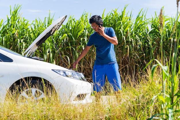 Un homme utilisant un téléphone alors qu'il avait une voiture à problèmes sur la route