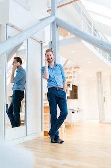 Homme utilisant un téléphone dans un bel appartement moderne portant une chemise