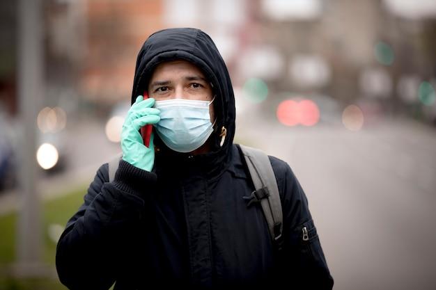 Homme utilisant un téléphone intelligent dans la ville portant un masque facial à cause de la pollution de l'air