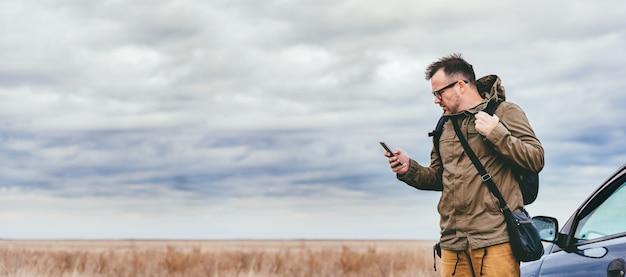 Homme utilisant un téléphone intelligent en plein air