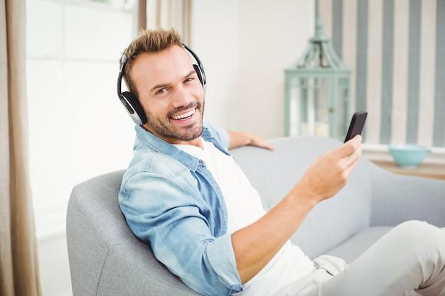 Homme utilisant un téléphone intelligent tout en écoutant de la musique