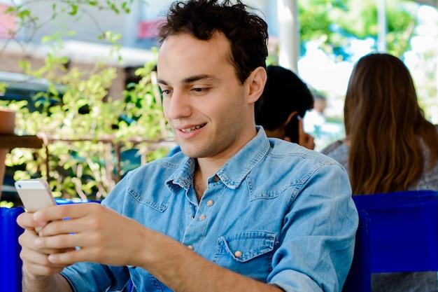 Homme utilisant un téléphone portable et buvant du café