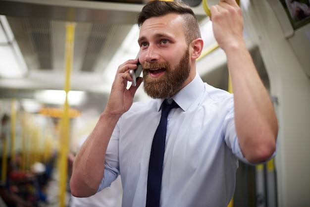 Homme utilisant un téléphone portable dans le métro