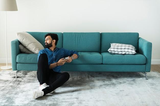 Homme utilisant un téléphone portable sur le sol seul
