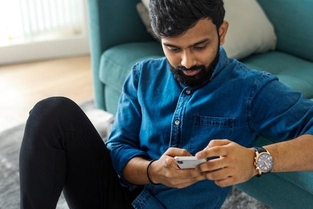 Homme utilisant un téléphone portable sur le sol