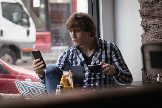 Homme Utilisant Un Téléphone Portable Tout En Prenant Un Café Photo gratuit