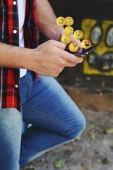Homme utilisant un téléphone pour envoyer des emojis