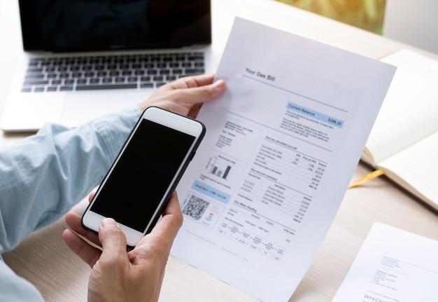 Homme utilisant le téléphone pour scanner le code qr afin de recevoir un rabais sur le paiement de factures d'électricité au bureau