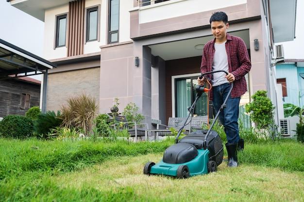 Homme utilisant une tondeuse à gazon coupant l'herbe à la maison