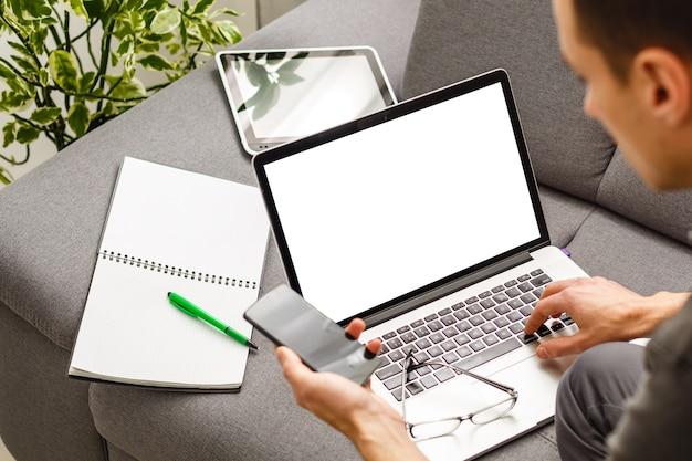 Homme utilisant, travaillant sur un ordinateur portable avec écran blanc dans le salon de la maison