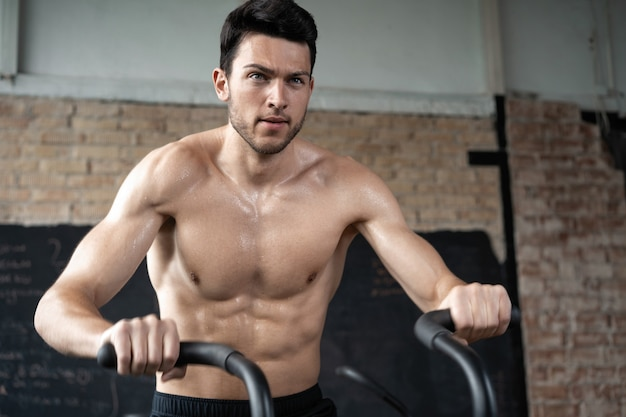 Homme utilisant un vélo d'exercice à la salle de sport. homme de remise en forme utilisant un vélo à air pour un entraînement cardio à la salle de sport d'entraînement fonctionnel.