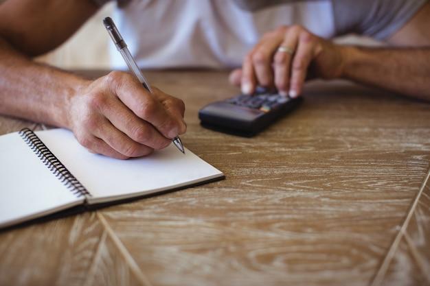Homme, utilisation, calculatrice, calculer, dépenses