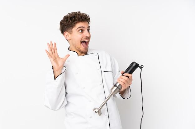 Homme, utilisation, mélangeur main, blanc, mur, surpris, expression faciale