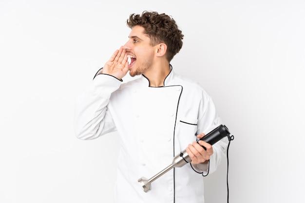 Homme, utilisation, mélangeur main, isolé, sur, mur blanc, criant, à, bouche grande ouverte