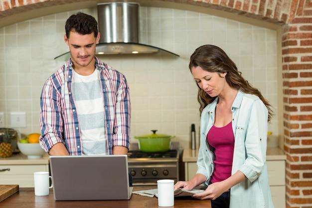 Homme, utilisation, ordinateur portable, et, femme, journal lecture, sur, worktop cuisine