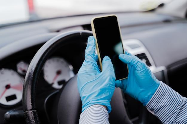 Homme, utilisation, téléphone portable, dans voiture, porter, masque protecteur, et, gants, pendant, pandémie