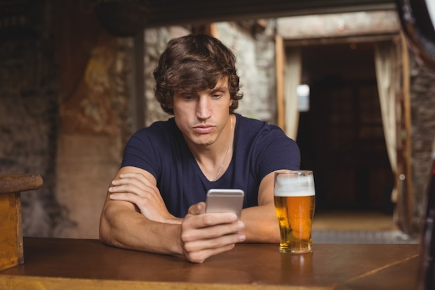 Homme, utilisation, téléphone portable, à, verre bière, sur, table