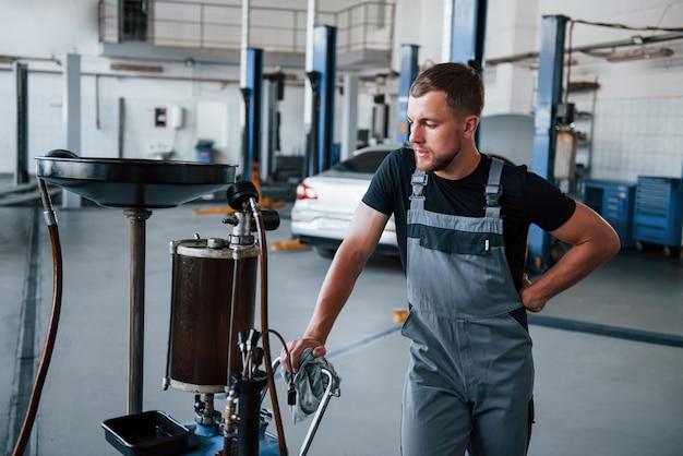 L'homme utilise un appareil spécial pour réparer une automobile cassée dans un garage