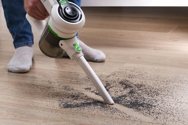 Un homme utilise un aspirateur sans fil vertical sans sac pour nettoyer le sol.