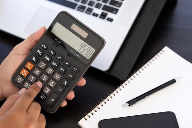 Homme utilise une calculatrice dans un bureau