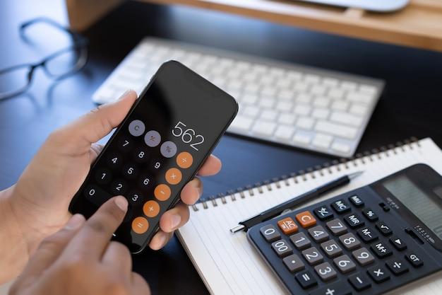 L'homme utilise une calculatrice pour calculer les coûts au bureau