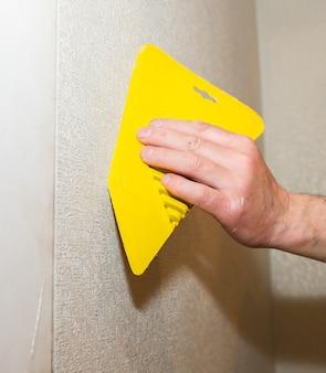 L'homme utilise un grattoir pour installer du papier peint. nivellement du mur. travaux de réparation d'entretien rénovation dans l'appartement. restauration à l'intérieur.