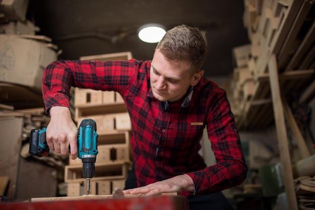 L'homme utilise une perceuse électrique dans l'atelier