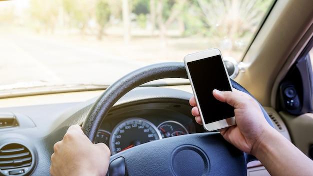 L'homme utilise un smartphone dans sa voiture.