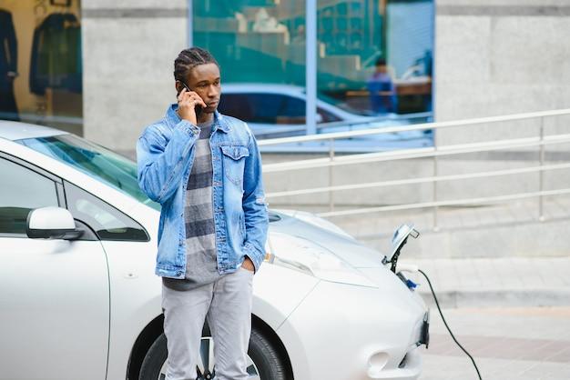 L'homme utilise un téléphone intelligent en attendant et l'alimentation se connecte aux véhicules électriques pour charger la batterie dans la voiture