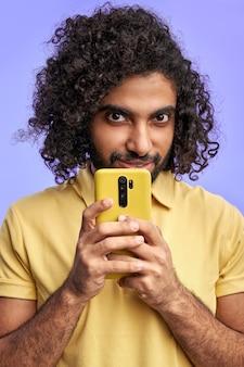 L'homme utilise un téléphone portable, tenez-le près du visage, regardez la caméra cachant quelque chose, message secret
