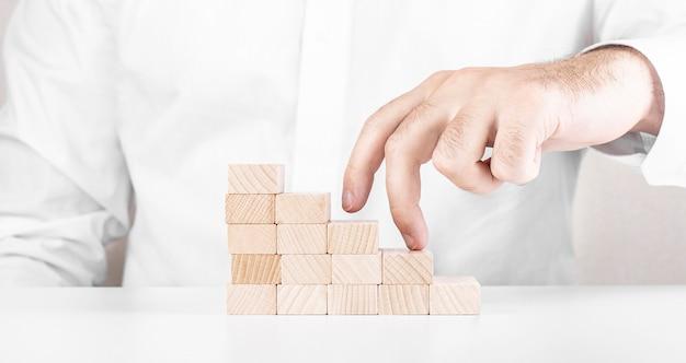 L'homme va au sommet de l'échelle à partir de blocs de bois
