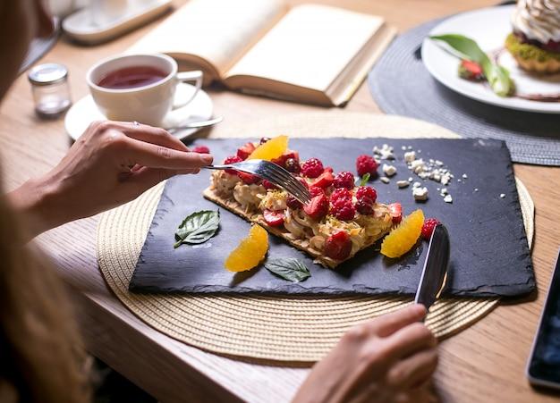 L'homme va manger la tarte napoléon à la crème framboise orange cerise guimauves menthe vue latérale