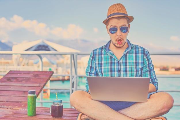 Homme en vacances, assis sur la jetée et travaille. guy choqué sur quelque chose sur un ordinateur portable