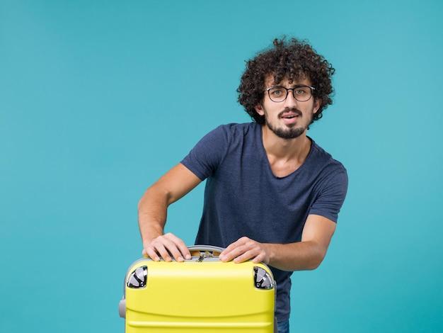 Homme en vacances avec grosse valise sur bleu clair
