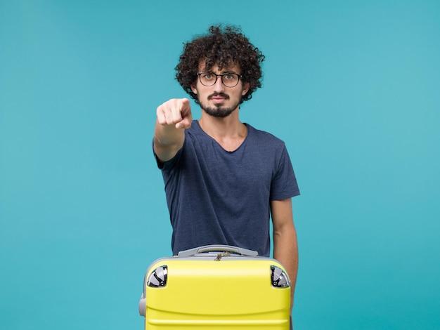 Homme en vacances avec grosse valise sur bleu