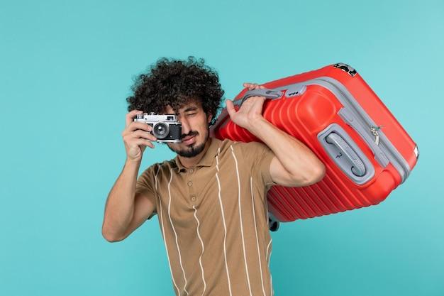Homme en vacances avec grosse valise prenant des photos avec appareil photo sur bleu