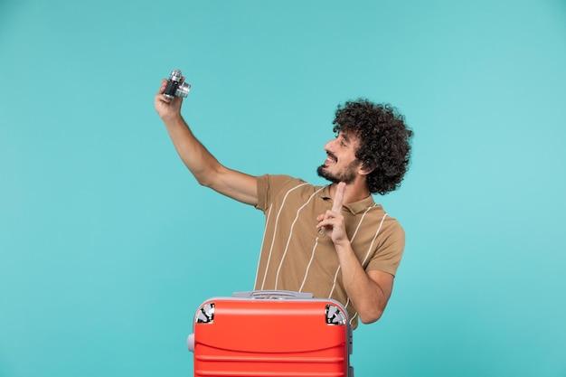 Homme en vacances avec une grosse valise rouge prenant des photos avec appareil photo sur bleu