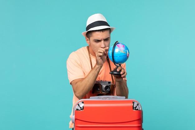 L'homme en vacances holding globe avec appareil photo sur bleu