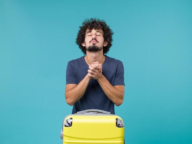 Homme en vacances priant sur bleu