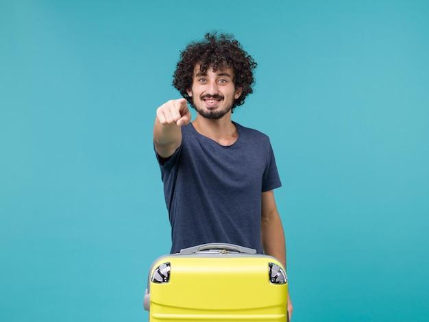 Homme en vacances souriant sur bleu