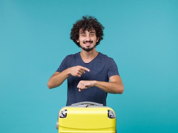 Homme en vacances souriant et vérifiant l'heure sur bleu